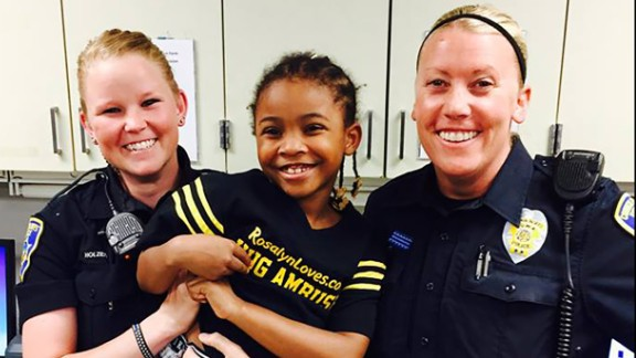Rosalyn Baldwin, 7, with two police officers of Council Bluffs Police Department in Iowa.