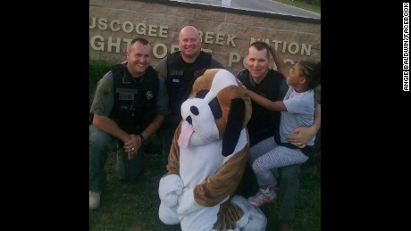 Three officers of Creek Nation Lighthorse Police host 7 year old Rosalyn Baldwin.