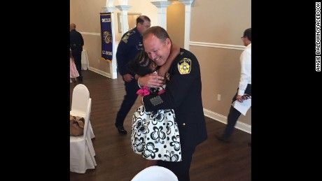 Rosalyn Baldwin, 7, hugs Sheriff Jason Ard of Livingston Parish, LA.