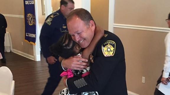 Rosalyn Baldwin, 7, hugs Sheriff Jason Ard of Livingston Parish, LA.