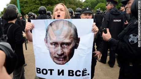 "A woman holds a poster bearint the portrait of the Russian President Vladimir Putin and reading ""that's all"" during an unauthorized opposition rally in centre of Saint Petersburg on June 12, 2017.  Authorities detained Russian opposition politician Alexei Navalny and hundreds of his supporters on Monday, as they mounted demonstrations across the nation against government corruption. Over 200 were detained in Moscow and Saint Petersburg an hour into the protest, according to an NGO that tracks arrests, with Navalny himself picked up by police in his building as he was headed to the event. / AFP PHOTO / OLGA MALTSEVA        (Photo credit should read OLGA MALTSEVA/AFP/Getty Images)"