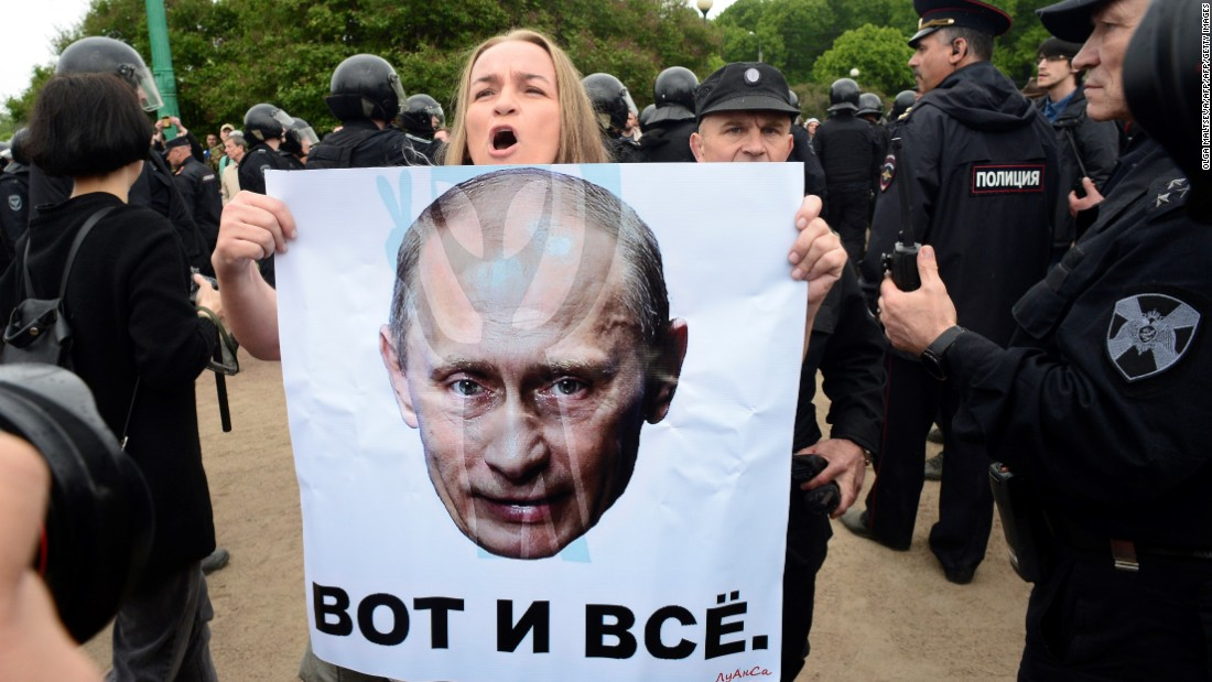 "A woman holds a poster bearing the portrait of Russian President Vladimir Putin which reads ""that's all"" during an unauthorized opposition rally in centre of Saint Petersburg."