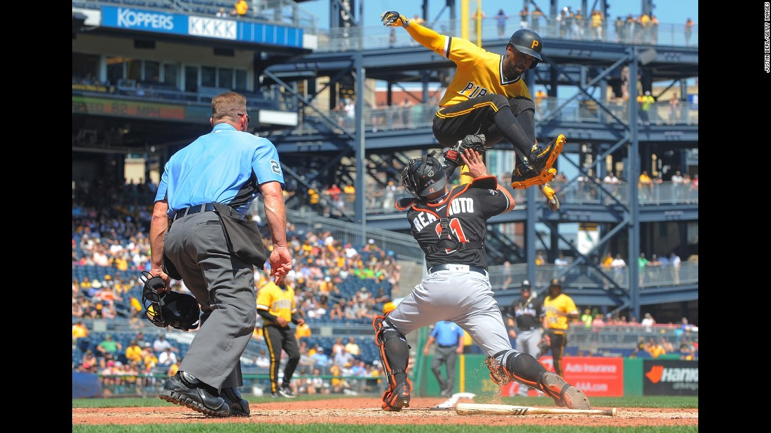 Pittsburgh's Andrew McCutcheon tries to jump over Miami catcher J.T. Realmuto, but he is tagged out at home during a Major League Baseball game in Pittsburgh on Sunday, June 11.