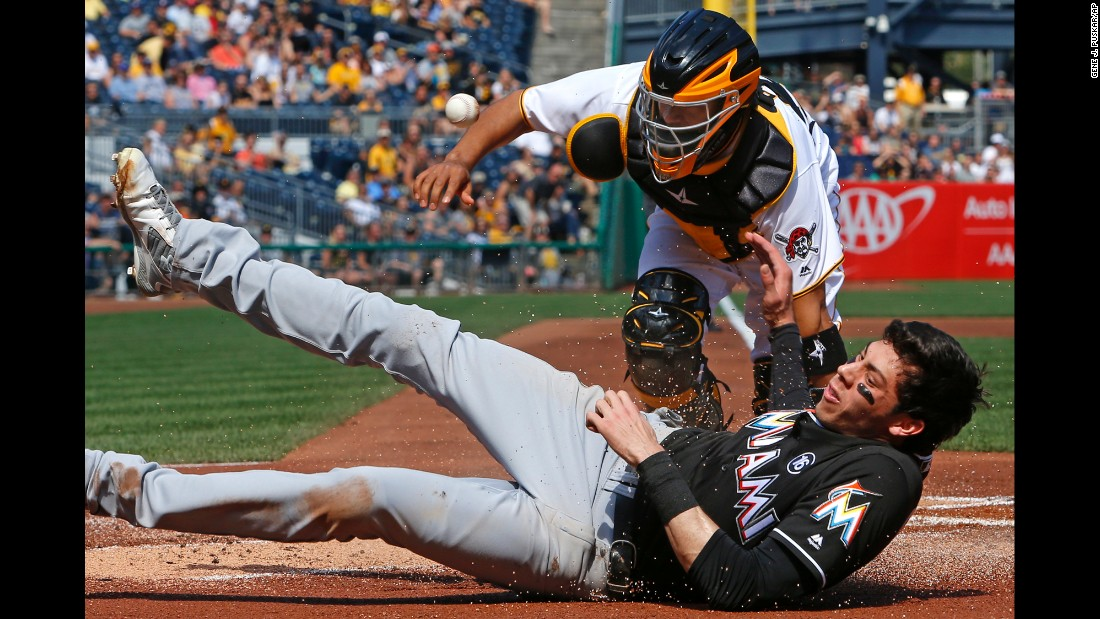The ball gets away from Pittsburgh catcher Elias Diaz as Miami's Christian Yelich scores a run on Saturday, June 10.