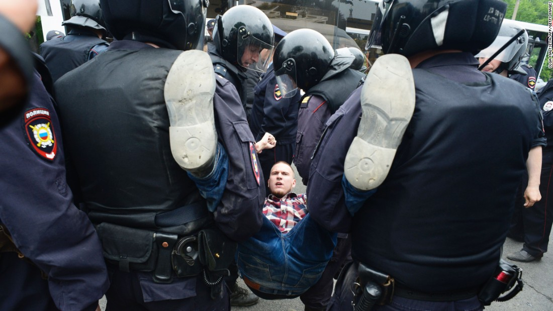 Russian police officers detain a participant of an unauthorized opposition rally in the center of Saint Petersburg on Monday, June 12.