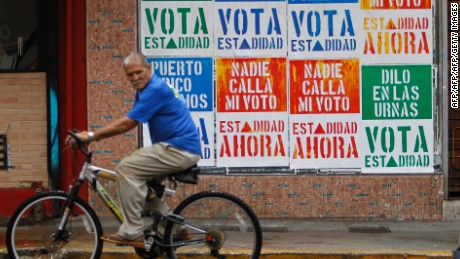 A rides his bicycle in front of a wall covered with campaign posters promoting Puerto Ricos statehood in San Juan, on June 9, 2017. A referendum on the political status of the US territory takes place on June 11, 2017. The US commonwealth of Puerto Rico votes on whether to become the 51st state. / AFP PHOTO / Ricardo ARDUENGO        (Photo credit should read RICARDO ARDUENGO/AFP/Getty Images)