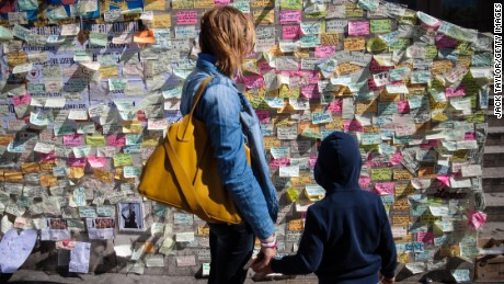 A woman and child look at messages of condolence on a wall on the south end of London Bridge.