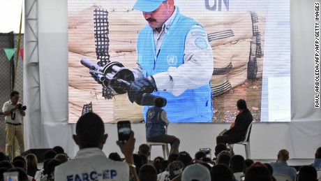 UN Secretary-General's Special Representative for Colombia and Head of the UN Mission to Colombia, Jean Arnault (C-L), and Revolutionary Armed Forces of Colombia (FARC) commander Pablo Catatumbo (C-R) look at a screen during a ceremony as part of the peace process in Buenos Aires, Cauca Department, Colombia on June 13, 2017.  Colombia's Marxist FARC rebels handed in rifles and grenade launchers Tuesday in what were described as meaningful strides toward a deadline for a total surrender of arms within one week. / AFP PHOTO / RAUL ARBOLEDA        (Photo credit should read RAUL ARBOLEDA/AFP/Getty Images)