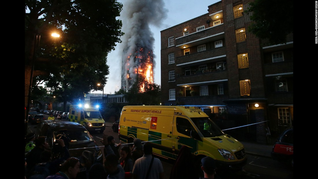 A security cordon holds people back as Grenfell Tower burns.