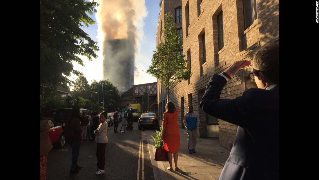 People watch as smoke rises from the tower.