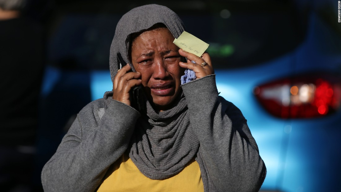 A woman cries as she tries to locate a missing relative.