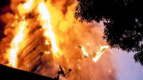 Burning debris falls from Grenfell Tower as a massive fire engulfs the London apartment building early on June 14, 2017. Seventy-two people are confirmed to have died in the fire.
