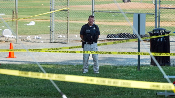 A police office stands watch behind police tape near strewn softballs on a field in Alexandria, Va., Wednesday, June 14, 2017, after a multiple shooting involving House Majority Whip Steve Scalise of La.
