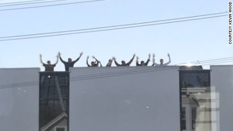 Employees at a UPS facility in San Francisco were asked to put their hands up as they left the building, according to Kevin Wood, who took this picture from his home across the street.