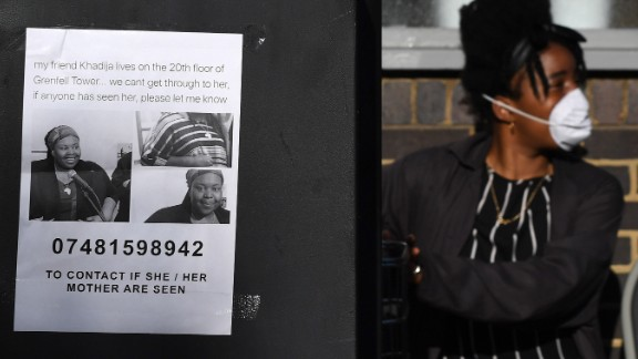 LONDON, ENGLAND - JUNE 14:  A missing person poster is displayed on a parking meter as a young girl with a face mask looks on near 24 storey residential Grenfell Tower block in Latimer Road, West London on June 14, 2017 in London, England.  The Mayor of London, Sadiq Khan, has declared the fire a major incident as more than 200 firefighters are still tackling the blaze, while at least 50 people are receiving hospital treatment.  (Photo by Chris J Ratcliffe/Getty Images)