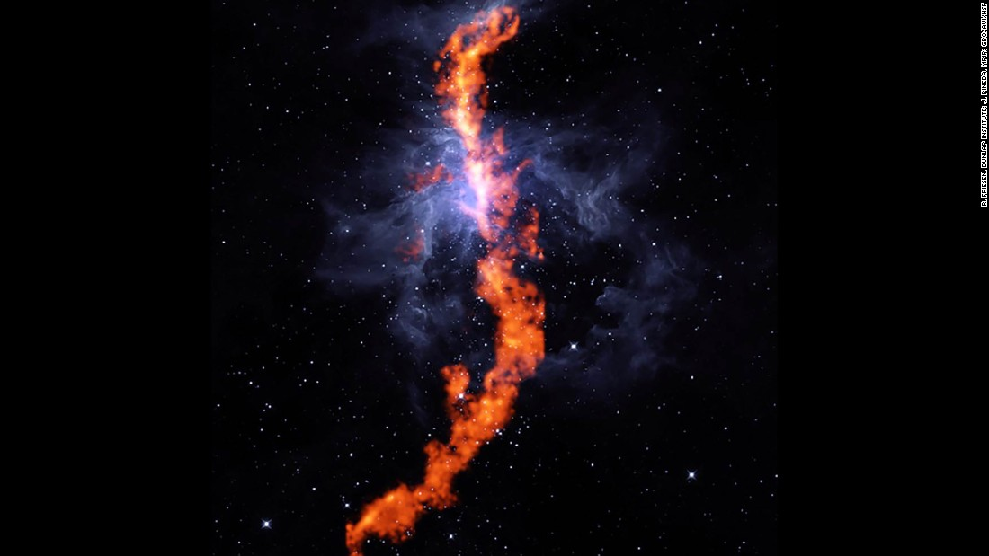 "This striking image is the stellar nursery in the Orion Nebula, where stars are born. The red filament is a stretch of ammonia molecules measuring 50 light-years long. The blue represents the gas of the Orion Nebula. This image is a composite of observation from the Robert C. Byrd Green Bank Telescope and NASA's Wide-field Infrared Survey Explore telescope. ""We still don't understand in detail how large clouds of gas in our Galaxy collapse to form new stars,"" said Rachel Friesen, one of the collaboration's co-Principal Investigators. ""But ammonia is an excellent tracer of dense, star-forming gas."""