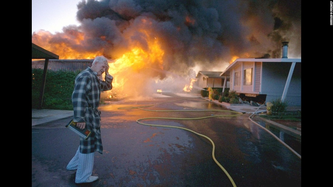 In the early morning hours of January 17, 1994, the 6.7 magnitude Northridge earthquake rattled the San Fernando Valley of Los Angeles, smashing buildings, toppling interstate highways and leading to at least 57 deaths. In this photo, Ray Hudson mourns the loss of a friend's home, shown engulfed in flames sparked by the earthquake. The quake was the costliest in US history, with damages topping $20 billion.