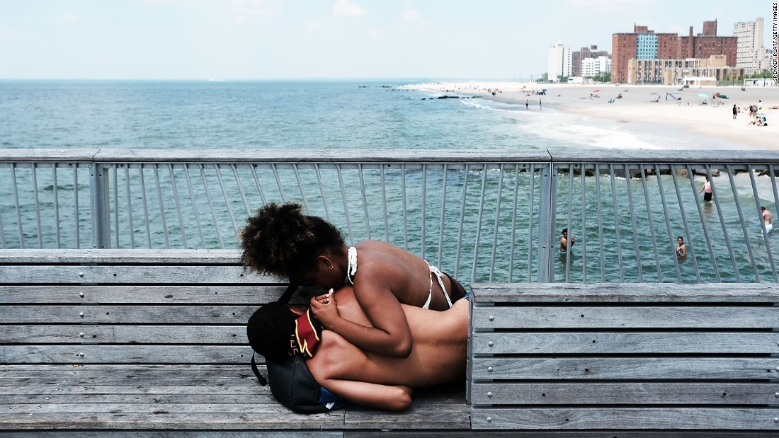 Teenagers relax on the Coney Island boardwalk Tuesday, June 13, in New York.