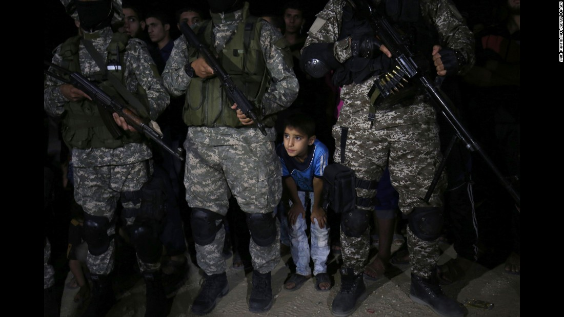 A child is seen with fighters from the Ezzedine al-Qassam Brigades, the armed wing of the Palestinian movement Hamas, during a memorial service in Gaza for leader Ibrahim Abu al-Naja on Saturday, June 10. Al-Naja was killed in an accidental explosion earlier this month, the group said.
