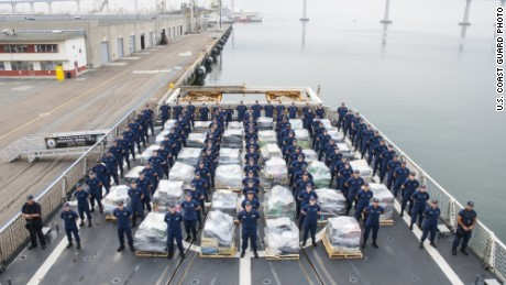 Crew members of the US Coast Guard Cutter Waesche stand guard over 18 tons of cocaine displayed on a San Diego pier.