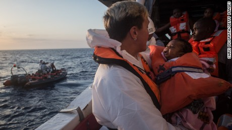 A crewmember from the Migrant Offshore Aid Station Phoenix vessel holds a child as they wait to transfer refugees