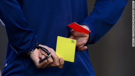English football referee Howard Webb keeps a red and a yellow card behind him during a seminar for 2014 FIFA World Cup referees on March 27, 2014 at the home of FIFA in Zurich, Switzerland. The seminar included fitness tests for 2014 FIFA World Cup, exercises with football players, physical exercises and theoretical sessions. AFP PHOTO / FABRICE COFFRINI        (Photo credit should read FABRICE COFFRINI/AFP/Getty Images)