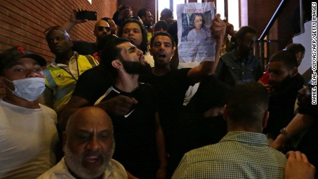 Protesters hold up pictures of missing loved ones Friday inside Kensington Town Hall.
