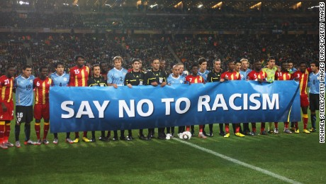 JOHANNESBURG, SOUTH AFRICA - JULY 02:  Players stand behind a 'Say No To Racism' banner prior to the 2010 FIFA World Cup South Africa Quarter Final match between Uruguay and Ghana at the Soccer City stadium on July 2, 2010 in Johannesburg, South Africa.  (Photo by Michael Steele/Getty Images)