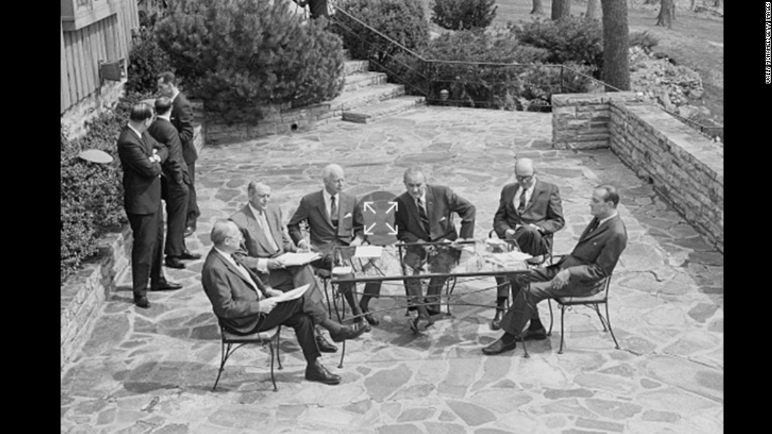 President Lyndon Johnson and members of his Cabinet hold an outdoor meeting on a Camp David patio to discuss the situation with the Vietnam War in April 1968.