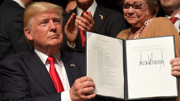 US President Donald Trump holds up a memorandum he signed on the US/ Cuba policy after he spoke at the Manuel Artime Theater in Miami, Florida on June 16, 2017.   / AFP PHOTO / MANDEL NGAN        (Photo credit should read MANDEL NGAN/AFP/Getty Images)