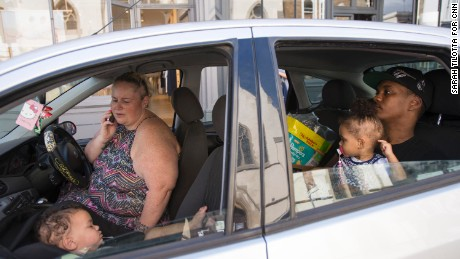 Emma Spinola talks on the phone outside Notting Hill Community Church as her baby sleeps in the front seat and husband Liniker minds their other child in the back.
