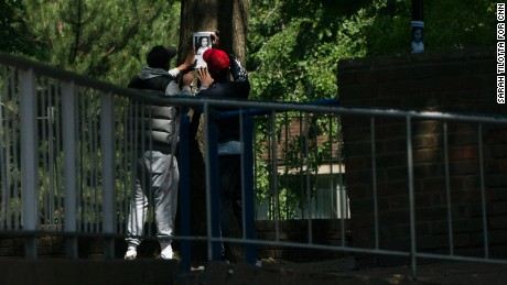 Two people work to tape a missing person's poster to a tree near Grenfell Tower.
