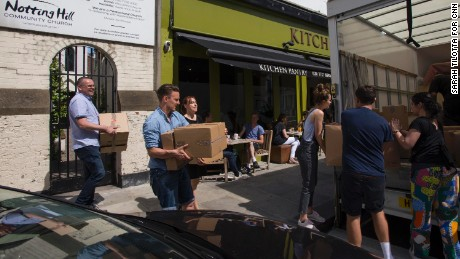 Associate pastor Danny Vance (in blue, second from left) carries donated goods to a waiting council van outside Notting Hill Christian Community Church.