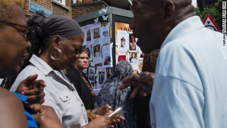 Community members exchange information near a poster board for the missing residents of Grenfell Tower.