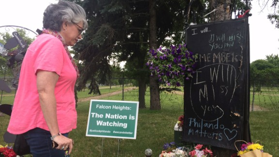 Theresa St. Aoro visits the memorial to place flowers at the site where Philando Castile was shot.