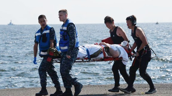 An injured USS Fitzgerald personnel is carried by US military solider on June 17.