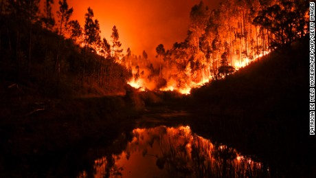 A wildfire is reflected in a stream at Penela, Coimbra, central Portugal, on June 18, 2017.  A wildfire in central Portugal killed at least 25 people and injured 16 others, most of them burning to death in their cars, the government said on June 18, 2017. Several hundred firefighters and 160 vehicles were dispatched late on June 17 to tackle the blaze, which broke out in the afternoon in the municipality of Pedrogao Grande before spreading fast across several fronts.  / AFP PHOTO / PATRICIA DE MELO MOREIRA        (Photo credit should read PATRICIA DE MELO MOREIRA/AFP/Getty Images)