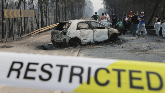 Firefighters and medical forensic investigators stand near a burnt car on the N236 road in central Portugal.