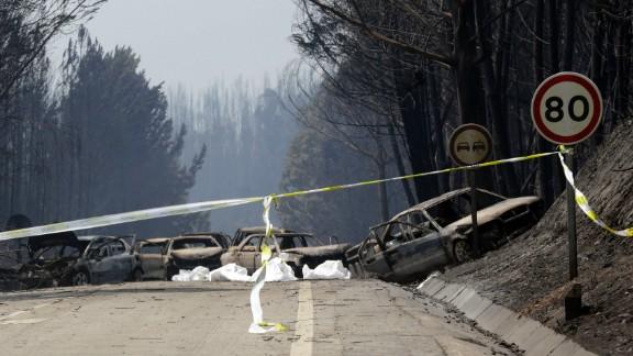 Burnt cars block the road between Castanheira de Pera and Figueiro dos Vinhos, central Portugal.