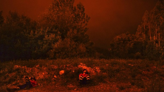 Firefighters rest after battling the wildfire in Penela, Coimbra, central Portugal.