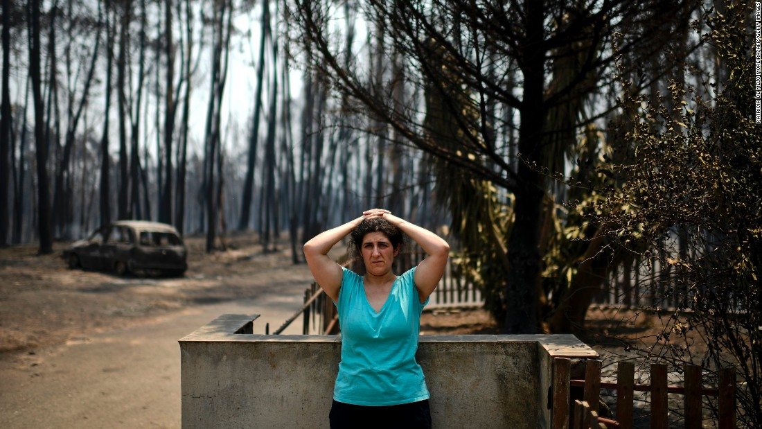 Anabela Silva stands in front of her house with her burnt car in the background after the wildfire burned through her property in Figueiro dos Vinhos.