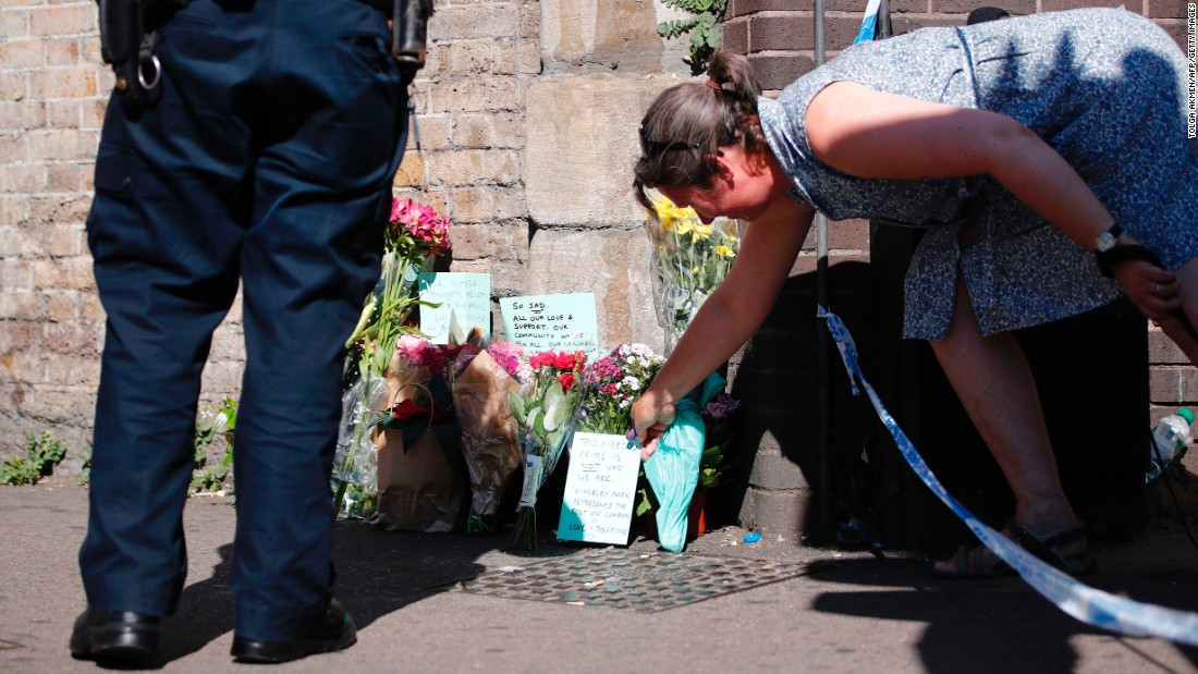 "A woman lays flowers near the scene where a van <a href=""http://www.cnn.com/2017/06/18/europe/urgent---london-vehicle-collision/index.html"" target=""_blank"">plowed into a crowd of pedestrians in north London</a> on Monday, June 19. A man was arrested, police said, and is being held on suspicion of terrorism offenses. The attack happened near a mosque, and British Prime Minister Theresa May said it was directed at Muslims."