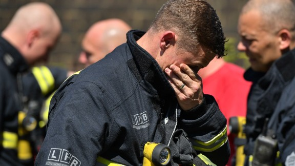 An emotional firefighter observes a moment of silence Monday near Grenfell Tower.