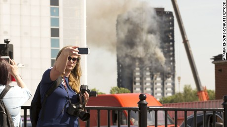 A woman takes a selfie as pedestrians stop to watch flames being put out at Grenfell Tower in the distance