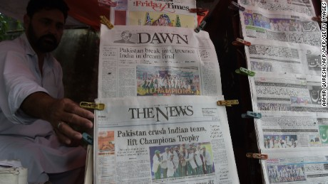 A Pakistani vendor arranges morning newspapers featuring front page coverage of Pakistan's victory against India in the ICC Champions Trophy final cricket match played in London, in Islamabad