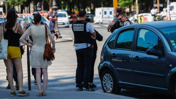 Police officers and pedestrians stand by a sealed-off area of the Champs-Elysees avenue in Paris after a car crashed into a police van Monday.