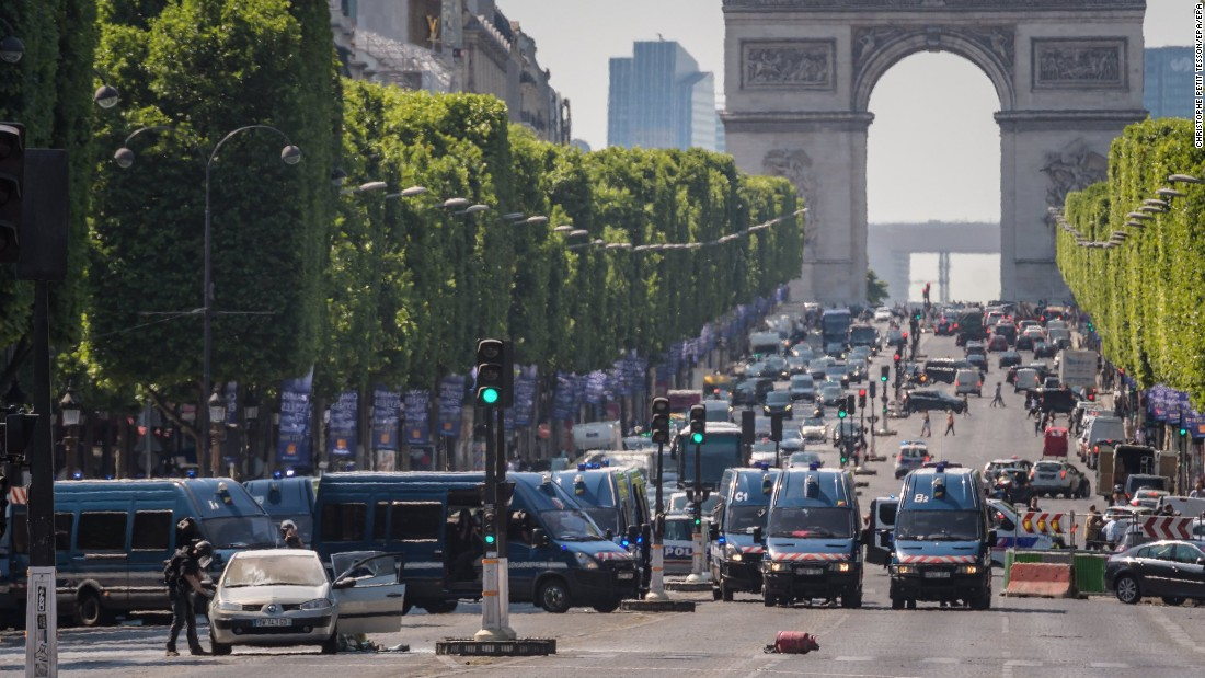 Police in Paris gather on the Champs-Elysees boulevard after an armed man intentionally rammed a car into a police van, authorities said on Monday, June 19. France's interior minister told reporters that the car contained weapons and explosives. The suspect later died.