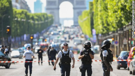 "Police officers and anti-riot police officers patrol the Champs-Elysees avenue on June 19, 2017 on the Champs-Elysees avenue in Paris, after a car crashed into a police van before bursting into flames, with the driver being armed, probe sources said. A source close to the investigation said the driver was ""seriously injured"".  / AFP PHOTO / ALAIN JOCARD        (Photo credit should read ALAIN JOCARD/AFP/Getty Images)"