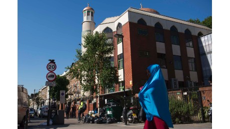 A woman in a blue hijab walks past the five-story red brick Finsbury Park Mosque -- the scene of Monday's attack.