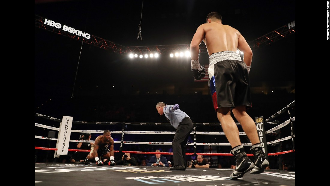 Referee Russell Mora directs Dmitry Bivol to a corner as Cedric Agnew tries to get up from the canvas on Saturday, June 17. Bivol won the light-heavyweight bout with a fourth-round stoppage.